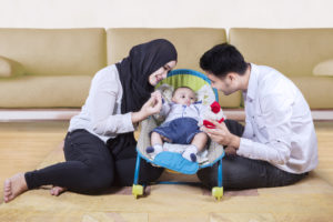 Parents sitting on floor playing with baby
